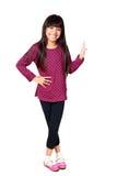 站立微笑的小亚裔的女孩举行某事 图库摄影