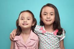 站立愉快的两个亚洲的孩子一起拥抱和 库存图片