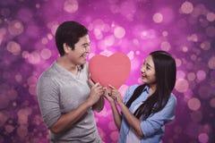 站立愉快的亚洲的夫妇拿着红色心脏 免版税库存照片