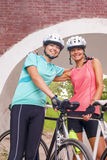 站立愉快的女性白种人的骑自行车者户外微笑 免版税图库摄影