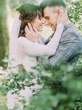 站立愉快的新婚佳偶的浪漫旁边画象势均力敌,当抚摸每个面颊时 公园构成 图库摄影