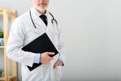 站立成熟的儿科医生采取笔记薄 免版税图库摄影