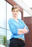 站立户外与胳膊的女实业家横渡 免版税库存照片