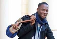 站立户外与袋子的愉快的非裔美国人的人 库存照片