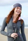 站立户外与水瓶的微笑的运动的妇女 免版税图库摄影