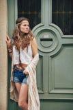 站立户外反对木门的时髦行家妇女 免版税库存照片