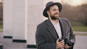站立户外和拍摄旅游sightseeings的帽子的时髦的年轻摄影师人在旅行期间 免版税库存图片
