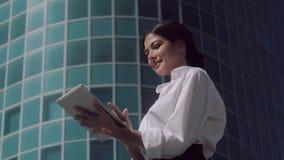 站立户外在一个晴天和工作在她的片剂的微笑的女商人 影视素材