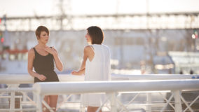 站立户外在桥梁的年轻可爱的女孩一起笑 免版税图库摄影