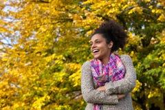 站立户外在秋天的愉快的少妇 库存图片