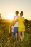 站立户外在领域拥抱的愉快的家庭 免版税库存图片