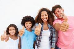 站立户外对白色墙壁的家庭给赞许 免版税库存图片