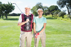 站立打高尔夫球的夫妇微笑对照相机 库存图片