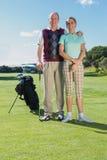 站立打高尔夫球的夫妇微笑对照相机 库存照片