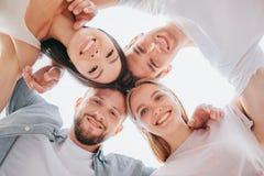 站立接近彼此和看下来在照相机的愉快和正面年轻人和妇女的垂直的图片 他们 免版税库存图片