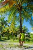 站立接近棕榈树的年轻美丽的亚裔女孩画象  免版税库存照片