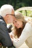 站立接近父亲的一个愉快的女儿的画象 免版税库存照片