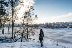 站立接近冻河的一个年轻美丽的红色头发欧洲女孩的画象近的冬天森林 免版税库存图片