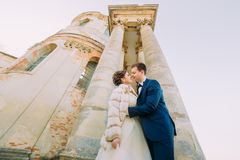 站立新婚佳偶的夫妇的浪漫照片势均力敌在古色古香的哥特式大厦的背景 图库摄影
