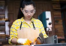 站立是运作被切开的木头的工艺在与圆锯的一个工作台的妇女电动工具在木匠机器 库存照片