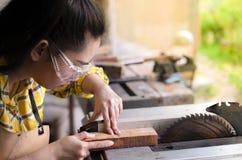站立是运作被切开的木头的工艺在与圆锯的一个工作台的妇女电动工具在木匠机器 免版税库存图片