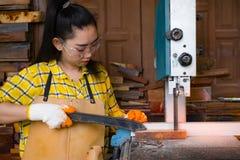 站立是运作被切开的木头的工艺在与带锯的一个工作台的妇女电动工具在木匠机器在车间 免版税库存图片