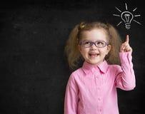 站立有电灯泡的玻璃的愉快的孩子近的学校黑板 免版税库存图片