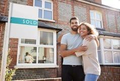 站立有被卖的标志的新的家外的激动的夫妇画象  免版税图库摄影