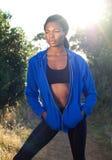站立本质上的蓝色运动衫的可爱的体育妇女 免版税库存照片