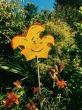 站立橙色冠的雕塑高与植物 库存图片