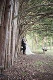 站立沿发球区域行的新娘和新郎  免版税库存图片