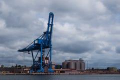 站立港口的起重机无所事事在多云天空下 免版税库存图片
