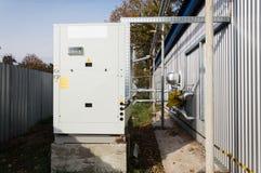 站立灰色商业的冷却装置室外在地面上近对现代制造业大厦 免版税库存照片