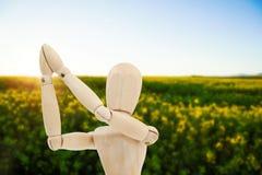 站立用两只手的木小雕象的综合图象被加入 免版税库存图片