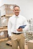 站立用在口袋举行的片剂个人计算机的手的经理 免版税库存图片