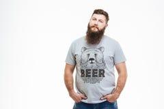站立用在口袋的手的严肃的可爱的有胡子的人 免版税库存照片