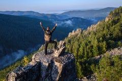站立用在山上面的被举的手和庆祝成功的愉快的人旅行家 库存图片