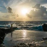 站立用在汹涌的海前面的被举的手的年轻人 免版税库存图片