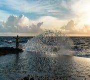 站立用在汹涌的海前面的被举的手的年轻人 库存照片