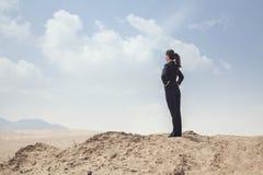 站立用在看在沙漠的臀部的手的年轻女实业家 库存照片
