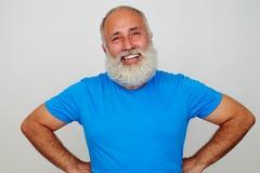 站立用在臀部和微笑的手的英俊的年迈的人 免版税库存图片