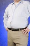 站立用在臀部的手的一个肥胖人 免版税库存照片
