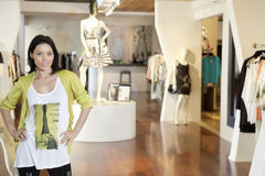 站立用在臀部的手的一名愉快的中间妇女的画象在时装商店 免版税库存照片