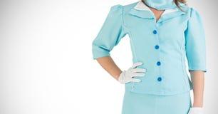 站立用在臀部的手的制服的空中小姐 免版税库存照片