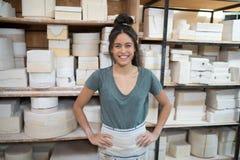 站立用在臀部的手的女性陶瓷工在瓦器车间 库存图片