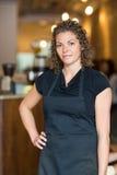 站立用在臀部的手的女服务员在咖啡馆 图库摄影