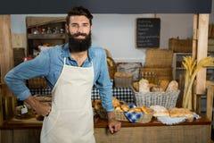 站立用在臀部的手的微笑的男职工画象在柜台 免版税图库摄影