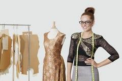 站立用在臀部的手的美丽的女性时装设计师画象在灰色背景 免版税库存图片