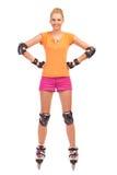 站立用在臀部的手的直排轮式溜冰鞋的妇女。 图库摄影