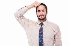 站立用在头的手的严肃的商人 免版税库存照片